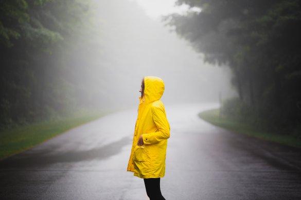 Mädchen steht in nebliger Landschaft mit gelbem Regenmantel