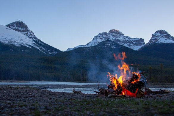 Campfire next to a lake on the mountains