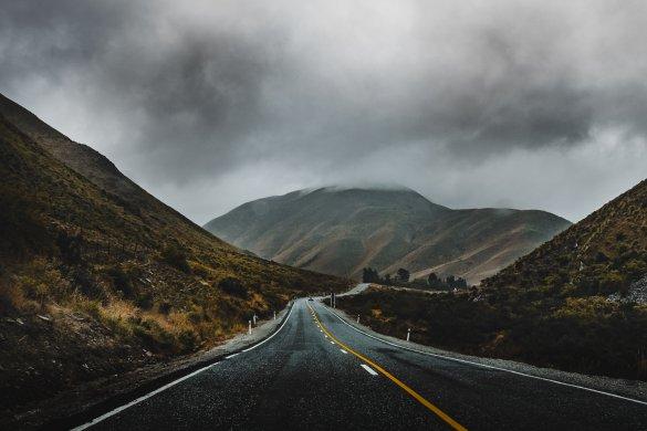 Neblige Straße umgeben von Bergen